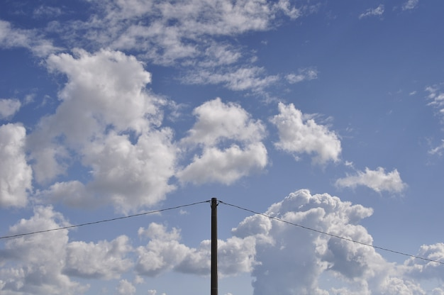 Beautiful shot of white clouds in the blue sky with an electricity pole in the middle