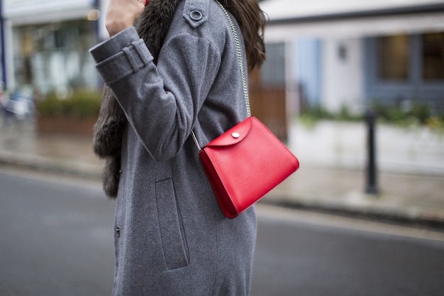 Beautiful shot of a white purse wearing by a lady on a dark coat on a road