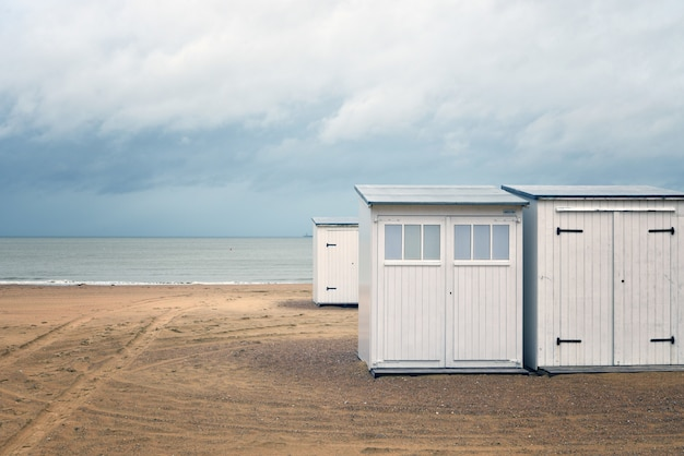 Beautiful shot of white small rooms on a beach shore near the water under a cloudy sky
