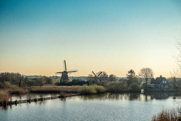 Beautiful shot of the windmill near the river surrounded by trees and houses