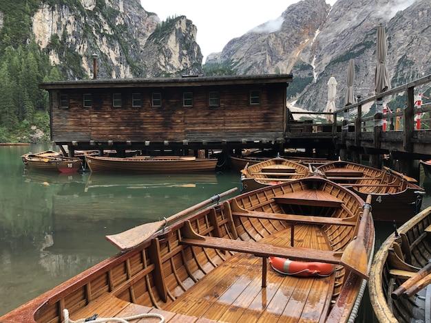 Beautiful shot of wooden boats on braies lake, on background of dolomites, trentino-alto adige,   pa