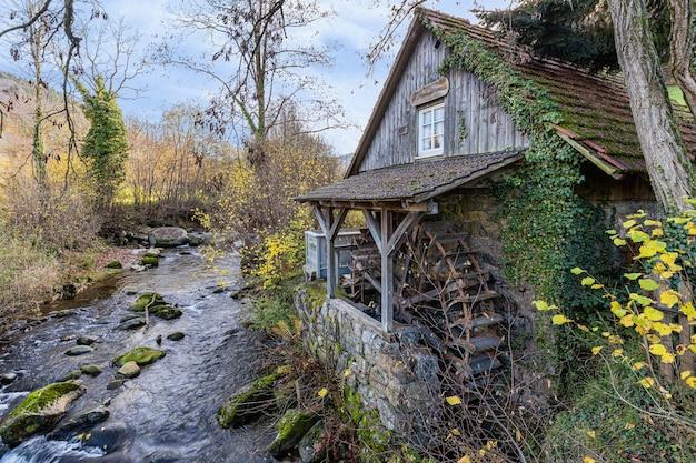 Bello scatto di una cabina di legno vicino a un fiume nelle montagne della foresta nera, germania