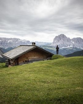 Bella ripresa di una casa in legno e di una persona nel parco naturale puez-odle a miscì, italia