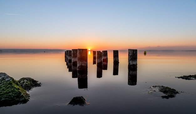 Beautiful shot of worn-out pier pillars on a body of water during sunset. perfect for a wallpaper