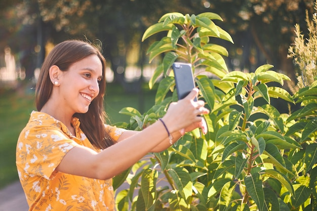 Bellissimo scatto di una giovane ragazza in una maglietta gialla che prende un selfie accanto ai cespugli