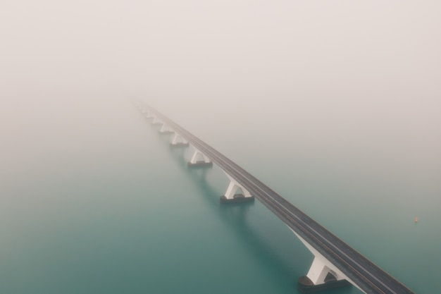 Beautiful shot of the zeeland bridge covered with fog in the netherlands