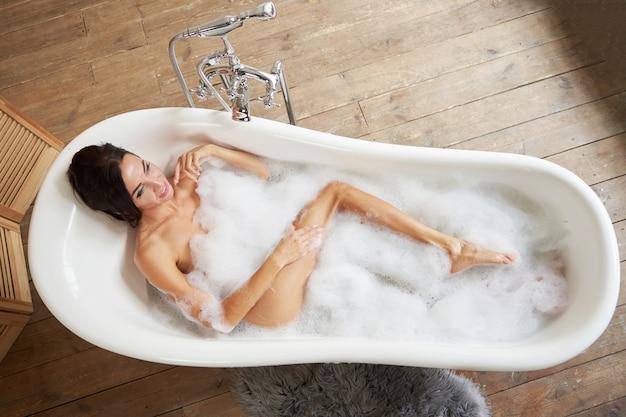 美しい華やかな女性は、明るいバスルームの泡沫状のバスルームに横たわって楽しんでいます。上からの眺め