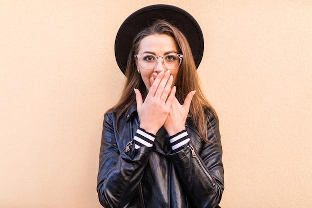 薄黄色の壁に分離された革のジャケットと黒い帽子の美しい恥ずかしがり屋のファッションの女の子