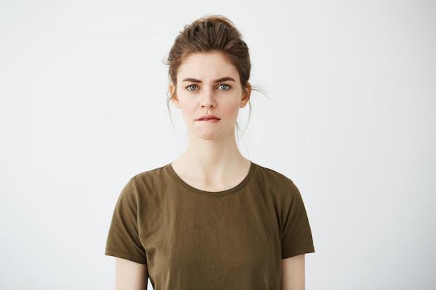Красивая застенчивая молодая женщина с волосами булочка мышления кусая губы.