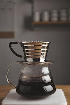 カフェショップの厚い木製のテーブルに隔離された、ローストフィルターコーヒーを備えた透明なクロームドリップコーヒーメーカーの美しい側面。白い重み。蒸気。残忍な。