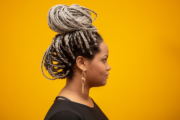 Beautiful side young african american woman with dread hair on yellow