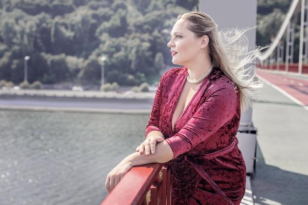 美しい光景。橋の上に一人で立っている間川を見ている素敵な思いやりのある女性