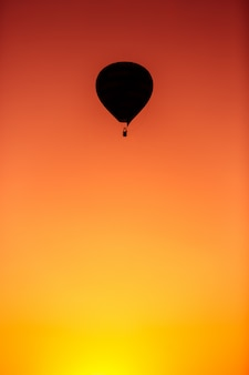 Beautiful silhouette of hot air balloon flying in sunset sky