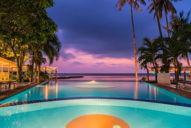 日の出時間にココナッツのヤシの木が付いているホテルのプールリゾートのプールの周りの美しいシルエットの豪華な傘と椅子 -