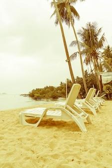 美しいシルエット日の出時間にココナッツパームツリーを備えたホテルプールリゾートのスイミングプール周りの豪華な傘と椅子 - ヴィンテージフィルターとブーストアップカラー処理