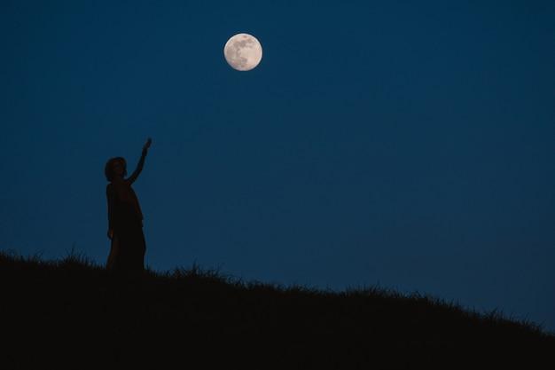보름달과 밤하늘의 배경에 대해 젊은 여자의 아름다운 실루엣