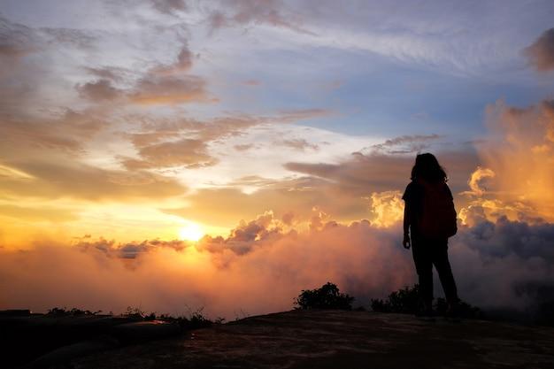 Красивый силуэт азиатской женщины с местом назначения и раем золотого восхода и захода солнца, сияющего туманом и туманом в джунглях на горе долины. концепция успеха и надежды на жизнь