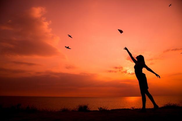 종이 비행기를 던지는 젊은 여자의 아름 다운 실루엣.