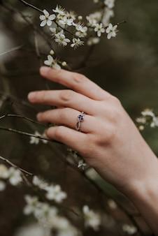 柔らかい女性の手に紫色のダイヤモンドが付いた美しいシルバーリング
