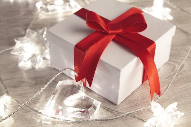 깜박이는 불빛으로 둘러싸인 빨간색 실크 테이프로 묶인 아름다운 간단한 빈 선물 상자. 세인트 발렌타인, 휴일, 축제, 생일을위한 낭만적 인 사랑스러운 선물