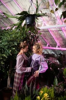 美しい姉妹。温室に立って顔を見合わせる魅力的なスタイリッシュな女性