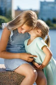 青いドレスを着た美しい姉妹が堤防に座っています