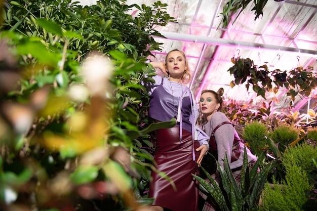 美しい姉妹。温室に立ちながらあなたを見ている素敵な魅力的な女性