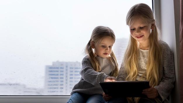 自宅でテクノロジーを使っている美しい姉妹