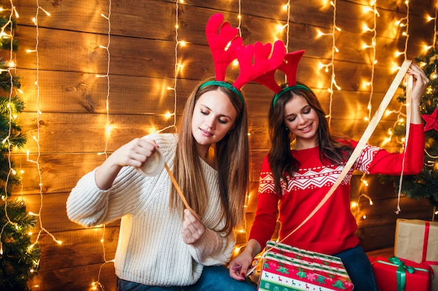 Beautiful sisters wrapping and decorating gift near christmas tree