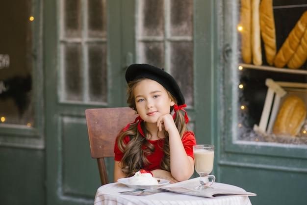 Красивая шестилетняя девочка в красном бархатном платье и черном берете сидит за столиком в кафе
