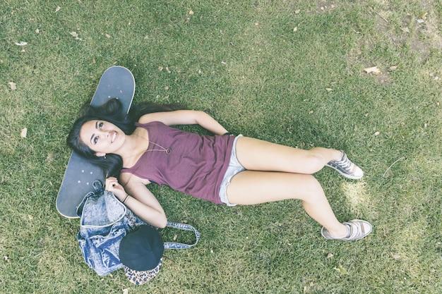 Beautiful skater girl relaxing at park, top view