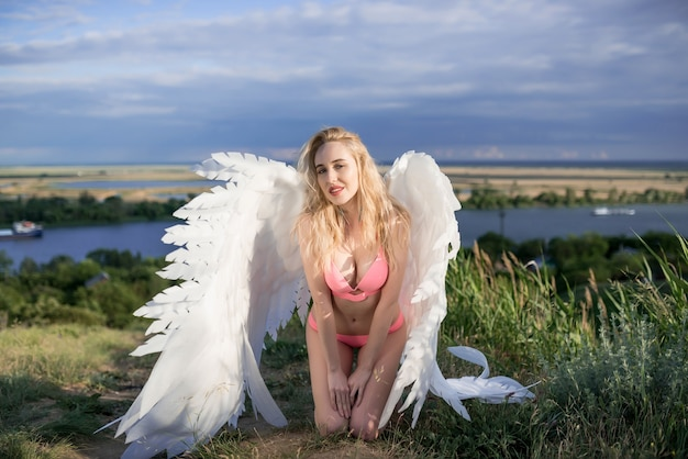 Beautiful skinny woman with white angel wings in a swimsuit posing