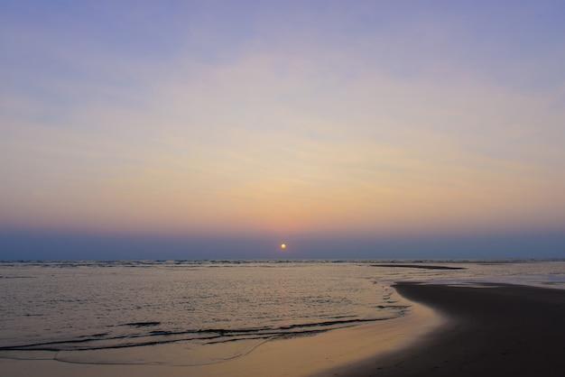 바다, 자연 풍경에 아름 다운 하늘 화려한 일몰. 황량한 해변, 태양은 바다 위의 구름에서 설정합니다.