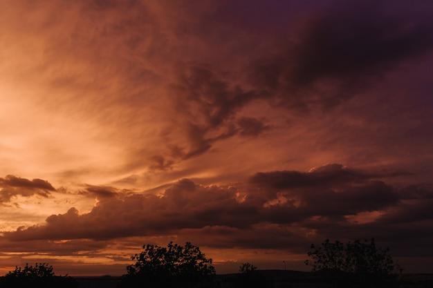日没の自然な背景の空にオレンジ色の雲と美しい空