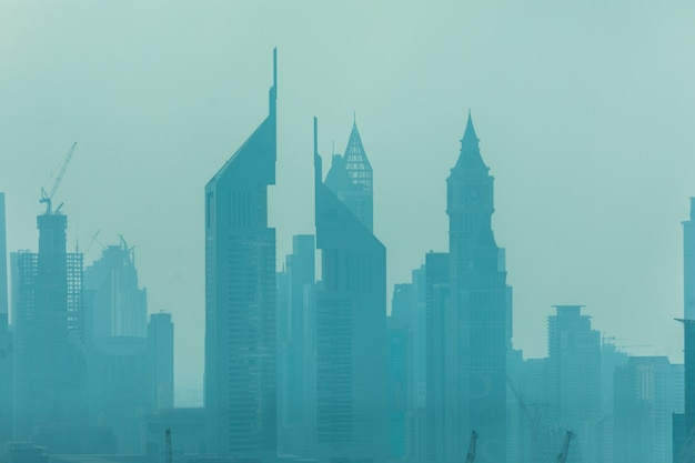 Beautiful skyline of dubai surrounded by sand dust at day light