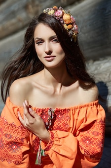 Beautiful slavic woman in an orange ethnic dress and a wreath of flowers on her head