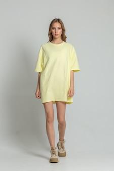 白いサイクロラマの黄色のtシャツでポーズをとって美しいスラブの若い女性