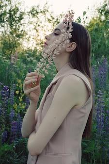 Красивая славянская молодая женщина позирует на открытом воздухе с цветком люпина в руке.