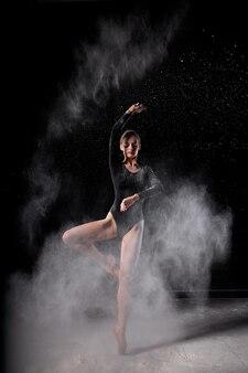 黒のボディスーツを着た美しい細身のバレエダンサーの女性は、黒のスタジオの背景で、彼女の体を覆う空飛ぶ小麦粉の中で官能的にポーズをとります。芸術的、商業的、モノクロのデザイン。