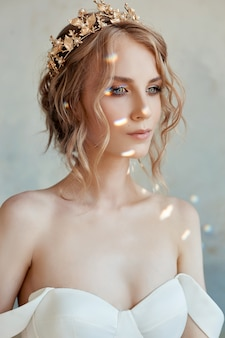 Beautiful slender blonde in the evening sun in a long white dress. portrait of a woman with a flower. perfect hairstyle and cosmetics of the bride, a new collection of wedding dresses