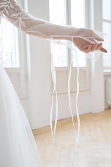 大きな窓の近くの長い白いドレスを着た夕方の太陽の下で美しい細いブロンド。