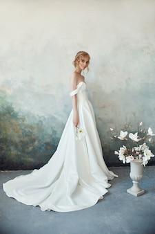 長い白いドレスを着た夕方の太陽の下で美しい細いブロンド。彼女の手に花を持つ女性の肖像画。花嫁の完璧なヘアスタイルと化粧品、ウェディングドレスの新しいコレクション