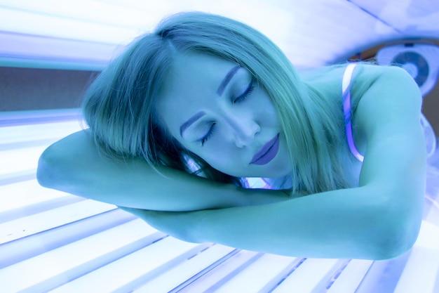Красивая стройная блондинка загорает в солярии. девушка в горизонтальном солярии лежа и улыбается. студия загара. спа.