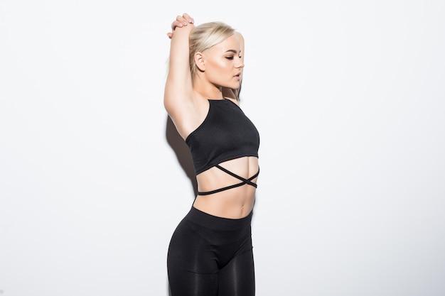 Bello modello femminile snello in vestiti di montaggio neri che posano sopra bianco