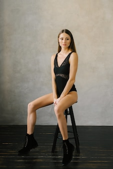 Beautiful slender girl in a black bodysuit sitting on a chair