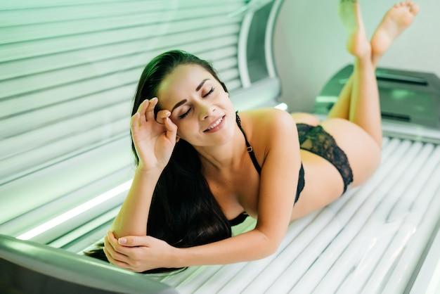 Красивая стройная девушка в купальнике лежит в горизонтальном солярии, загорая под ультрафиолетовыми лучами