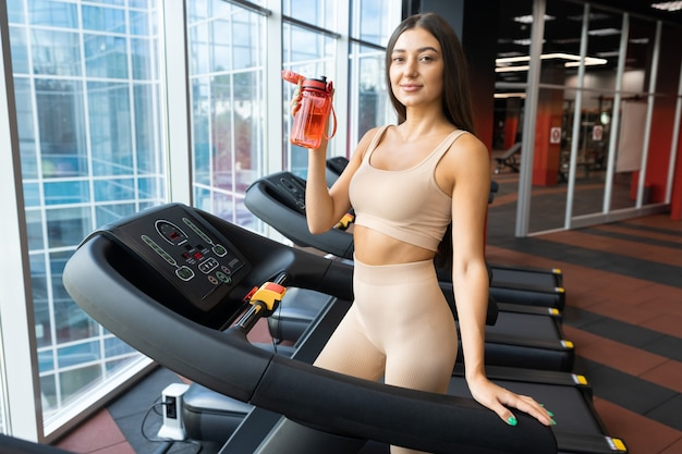 Beautiful slender girl stands with a bottle on a treadmill