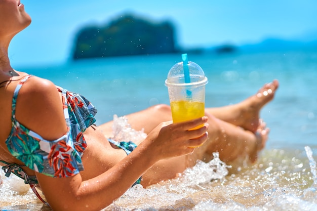A beautiful slender girl in a swimsuit enjoys a tan while lying on a tropical beach