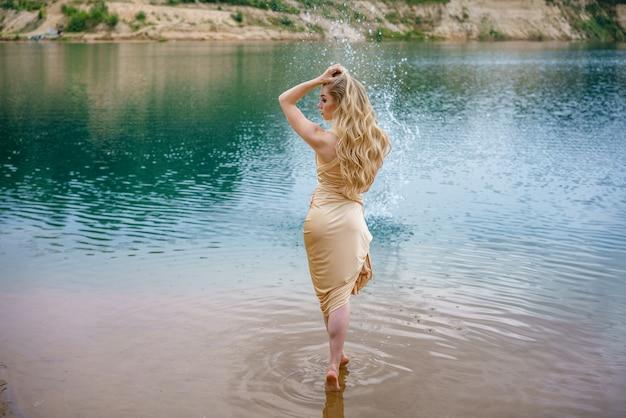 Красивая стройная девушка с длинными волосами позирует стоя в воде