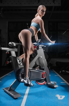 Beautiful slender and long-legged girl sits on an exercise bike. back view.